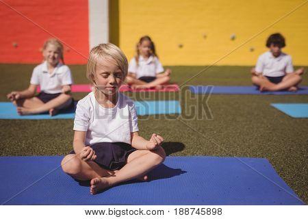 Schoolkids practicing yoga in schoolyard