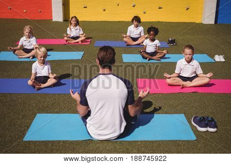 Coach and schoolkids practicing yoga in schoolyard