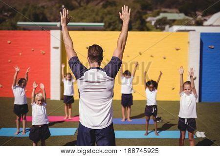 Coach teaching exercise to school kids in schoolyard