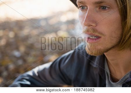 Thoughtful man exhaling smoke in the park