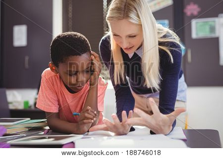 Teacher helping schoolgirl with her homework in classroom at school