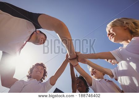 Happy coach and schoolkids forming handstack in schoolyard