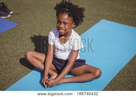 Portrait of smiling schoolgirl exercising in schoolyard
