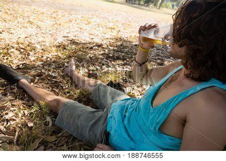 Unconscious drunken man drinking beer in the park