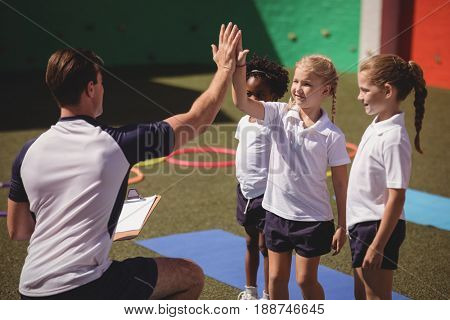 Coach and schoolkids giving high five to each other in schoolyard