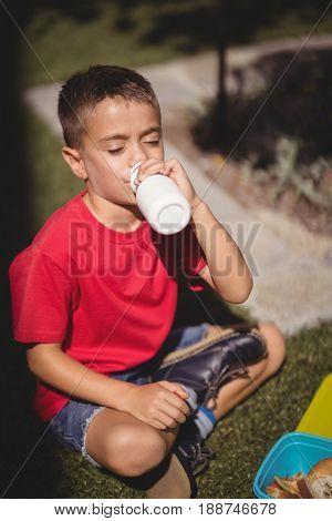 Schoolboy drinking juice in schoolyard at school