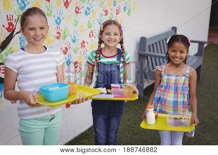 Portrait of happy schoolgirls holding meal in tray at school