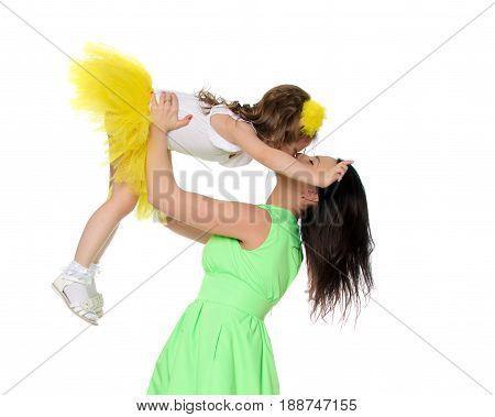 Beautiful young mother in a short green dress and her little beloved daughter in a yellow skirt.Fun mother throws daughter on hands.Turning sideways to the camera.Isolated on white background.
