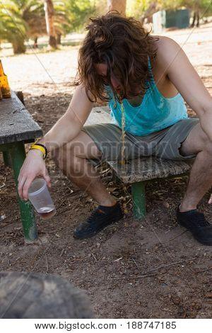 Drunken man vomiting in the park
