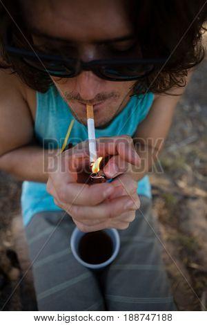 Drunken man smoking cigarette in the park