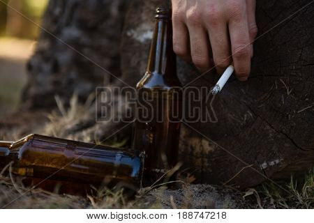 Hand of drunken man holding a cigarette in the park