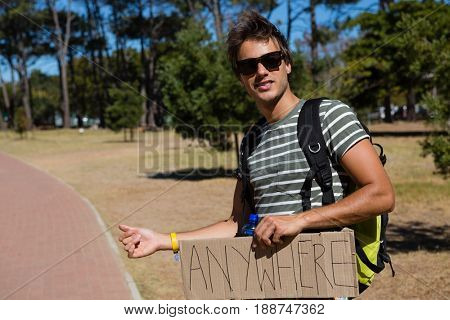Man hitchhiking at roadside on a sunny day