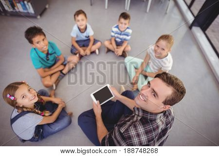 Overhead view of teacher and schoolkids using digital tablet in library at school