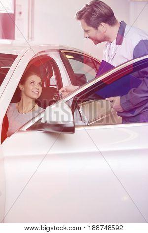 Automobile mechanic giving car key to female customer in repair shop