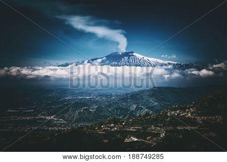 Smoking Mount Etna volcano, as seen from Taormina, Sicily