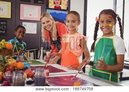 Portrait of smiling teacher and schoolkids standing in drawing classroom