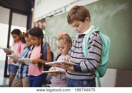 Attentive schoolkids using digital tablet in classroom at school