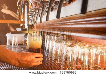 Bartender hand pouring draught beer to glass from a pub tap