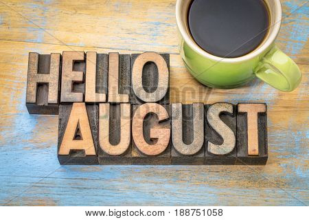 Hello August- word abstract in vintage letterpress wood type blocks against grunge wooden background with a cup of coffee