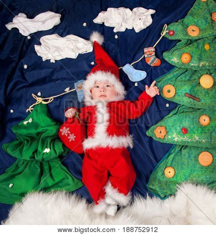 Infant baby boy wearing Santa costume holding bag with gifts. Posing against textile decoration of a christmas trees decorated cookies and sweets