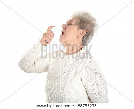 Senior ill woman using spray, isolated on white. Concept of allergy