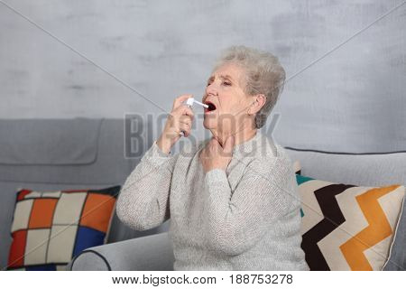 Senior ill woman using spray at home. Concept of allergy