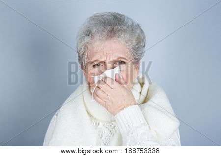 Mature ill woman with tissue on color background. Concept of allergy