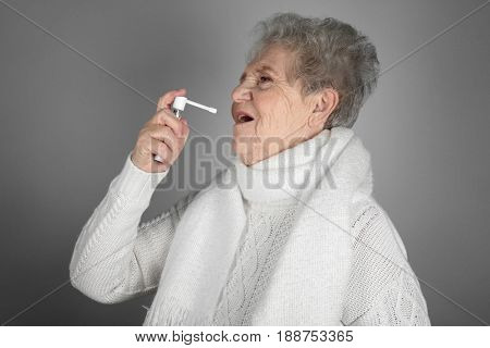 Senior ill woman using spray on grey background. Concept of allergy