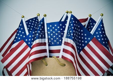 closeup of some flags of the United States in a brown paper shopping bag, with a vignette added