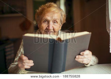 Russian elderly woman reading a book.