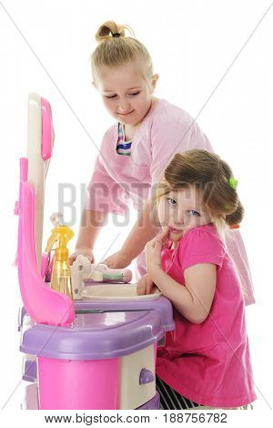Young sisters playing beauty salon. The younger one looks shy as her sister's deciding what to do next.  Focus on younger girl.  On a white background.
