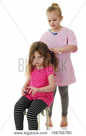 An unhappy preschooler pouting as her young elementary sister brushes her hair. On a white background.
