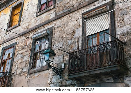 Facade of abandoned house buildings, Porto, Portugal. Ancient ruins of Europe.