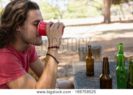 Man drinking beer from disposable glass in the park