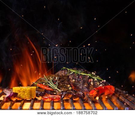Beef steaks with vegetable on the grill grate, flames on background. Barbecue and grill, delicious food.