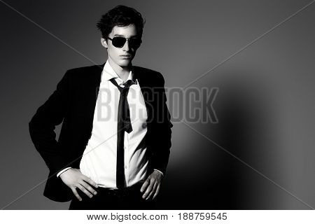 Fashion shot. Black-and-white portrait of a handsome young man posing in elegant black suit, white shirt and sunglasses. Studio shot.