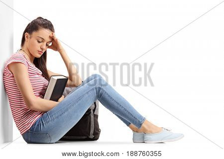 Depressed teenage student sitting on the floor and leaning against a wall isolated on white background