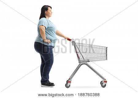 Full length profile shot of a woman with an empty shopping cart waiting in line isolated on white background