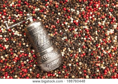 Pepper mill and hot pepper seeds. Red, black and white pepper closeup on rustic market