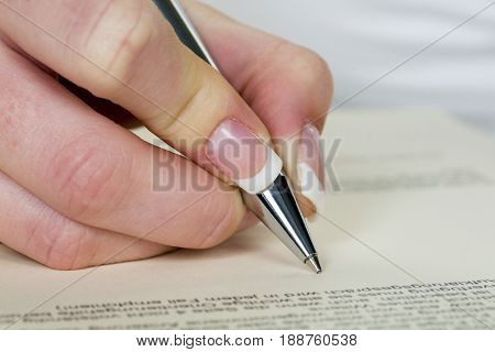 hand with fountain pen signing contract