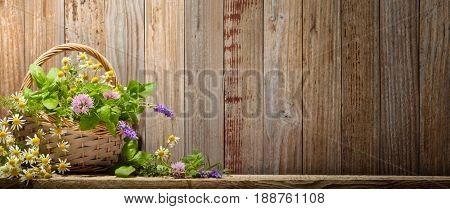 Basket with herbs on wooden background