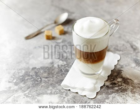 Glass of Latte Macchiato on stone background