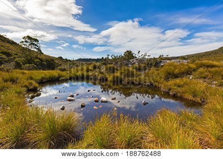 Blue sky and clouds reflecting on water surface of a pond near Dove Lake at Cradle Mountain - Lake St Clair National Park. Autumn in Tasmania, Australia