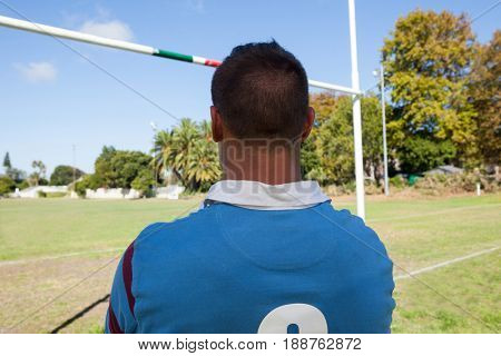 Rear view of rugby player standing against blue sky at playing field
