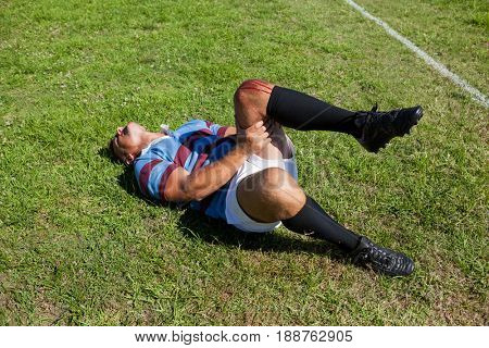 Full length of rugby player with injured knee lying on field during sunny day