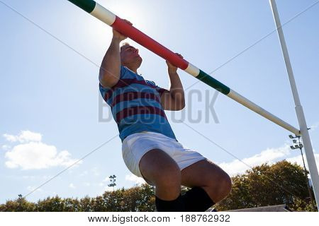 Low angle view of rugby player exercising on goal post against sky during sunny day