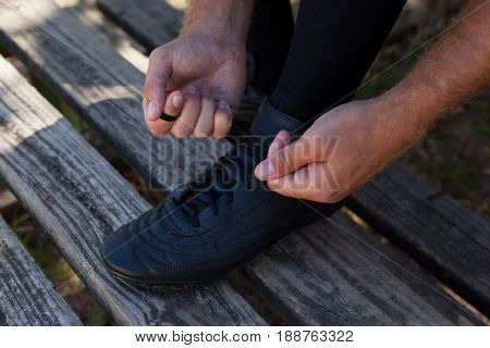 Low section of player tying shoes on wooden bench