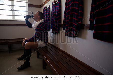 Tired player drinking water while sitting on bench against clothes rack in locker room