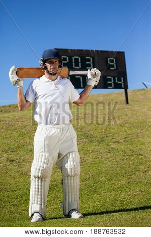 Full length of cricket player holding bat while standing on field
