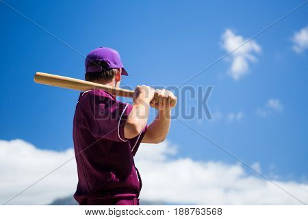 Low angle side view of baseball player holding bat against blue sky on sunny day